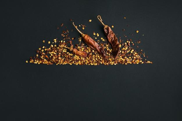 Cornice di pepe di caienna rosso tritato, fiocchi di peperoncino essiccato e semi su fondo nero. spezie fatte in casa ingredienti per cucinare. condimenti per cornice alimentare