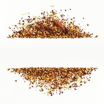 Cornice di pepe di caienna rosso tritato, fiocchi di peperoncino essiccato e semi isolati su un bianco