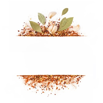 Cornice di pepe di caienna rosso tritato, fiocchi di peperoncino secco, semi, foglie e aglio isolato su un bianco