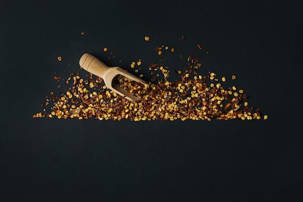 Cornice di pepe di caienna rosso tritato, fiocchi di peperoncino secco, semi e cucchiaio di legno su un nero. spezie fatte in casa ingredienti per cucinare. condimenti per cornice alimentare