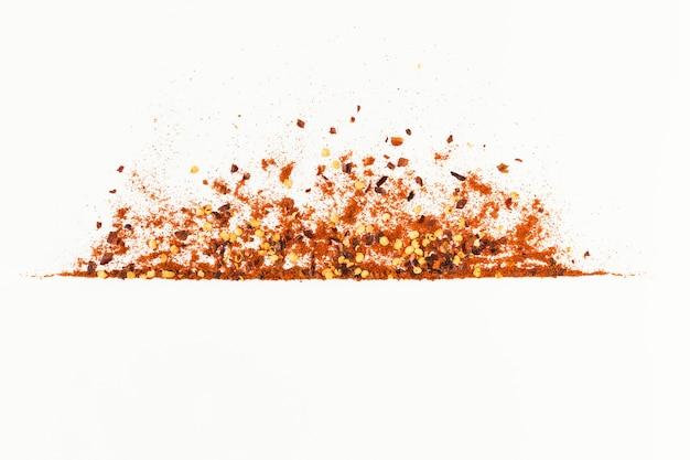 Cornice di pepe di cayenna rosso tritato, paprica di carta rossa, fiocchi di peperoncino essiccato e semi isolati su uno sfondo bianco