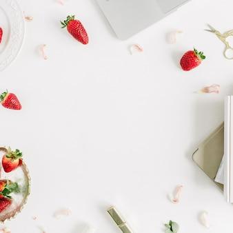 Cornice di una scrivania da ufficio moderna femminile con laptop, notebook, rossetto, fragole fresche crude e boccioli di fiori rosa su sfondo bianco. lay piatto