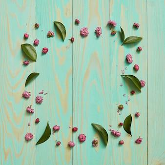 Cornice di fiori e foglie su uno sfondo blu in legno piatto laici
