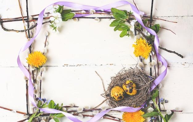 Cornice di fiori nidificano con uova primavera composizione pasquale
