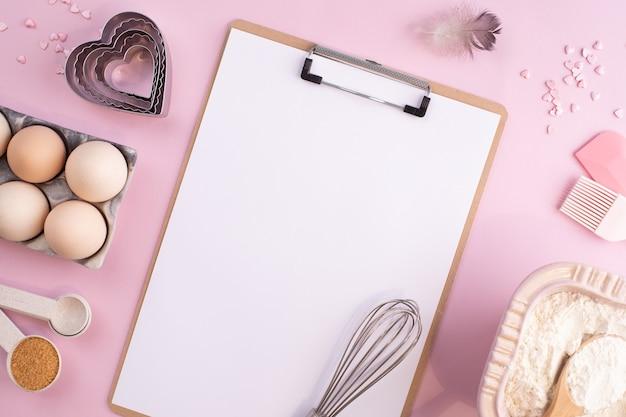 Cornice di ingredienti alimentari per la cottura su una superficie pastello delicatamente rosa