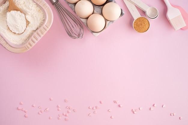 Cornice di ingredienti alimentari per cuocere su un tavolo pastello delicatamente rosa. cucinare laici piatta con copia spazio. vista dall'alto. concetto di cottura. laici piatta