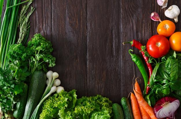 Cornice di verdure fresche su fondo in legno con copia spazio