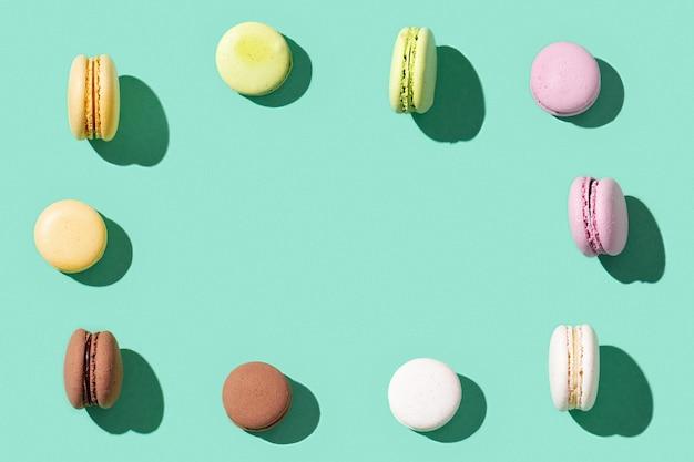 Cornice da amaretti assortiti su colore verde blu brillante, macarons colorati biscotti francesi