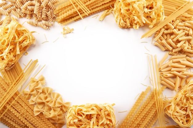 Cornice da varietà assortite di carta da parati con pasta. mescolare maccheroni, spaghetti su sfondo bianco con spazio di copia