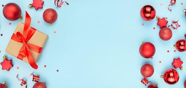 Cornice di giocattoli di natale e un regalo su sfondo blu. sfondo di natale. banner di capodanno.