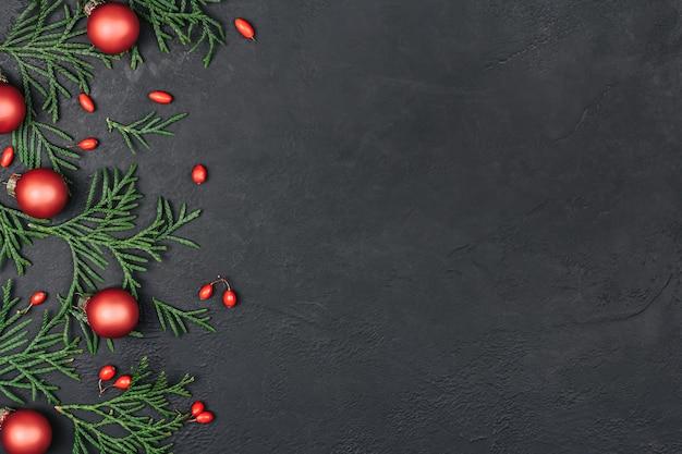 Cornice di ramoscelli verdi e palle di natale rosse su fondo nero