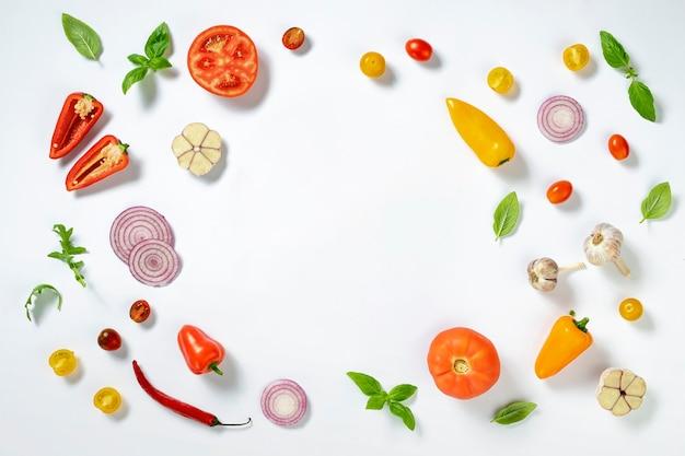 Cornice di ingredienti per cucinare la pizza italiana fatta in casa su sfondo bianco, vista dall'alto piatta