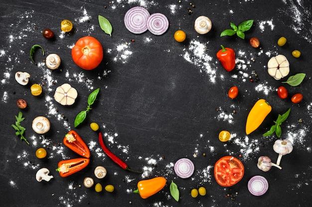 Cornice di ingredienti per cucinare pizza italiana fatta in casa su sfondo di pietra nera vista dall'alto