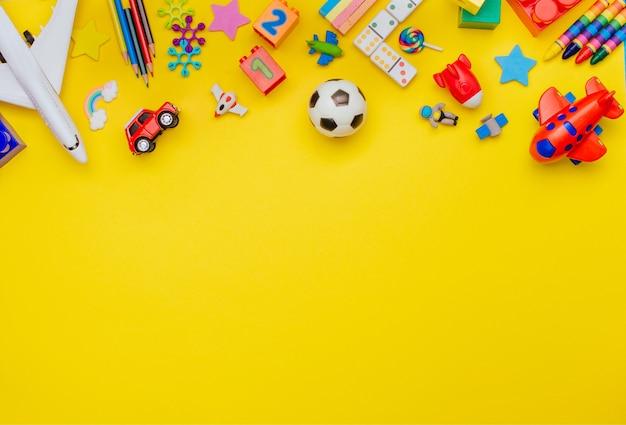 Cornice di giocattoli per bambini su sfondo giallo con uno spazio vuoto per il testo.
