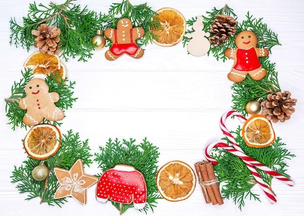 Cornice fatta di biscotti di natale e albero di abete su sfondo bianco.