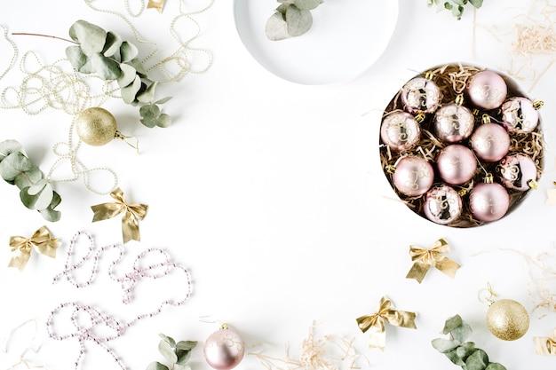 Cornice fatta di decorazioni natalizie con palline di vetro natalizie, orpelli, fiocco, eucalipto.