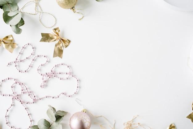 Cornice fatta di decorazioni natalizie con palline di vetro natalizie, orpelli, fiocco, eucalipto. Foto Premium