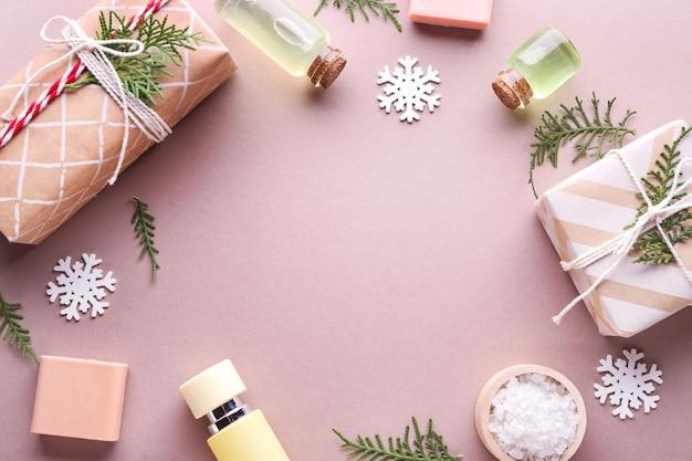 Cornice realizzata con scatole regalo natalizie e prodotti per trattamenti termali su superficie colorata