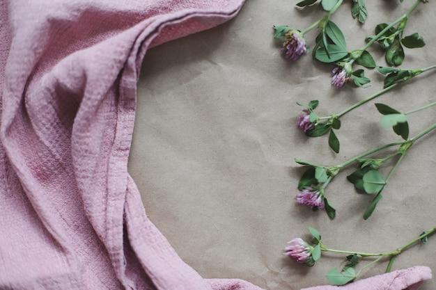 Cornice realizzata con fiori di trifoglio e tessuto rosa con vista dall'alto flatlay copyspace