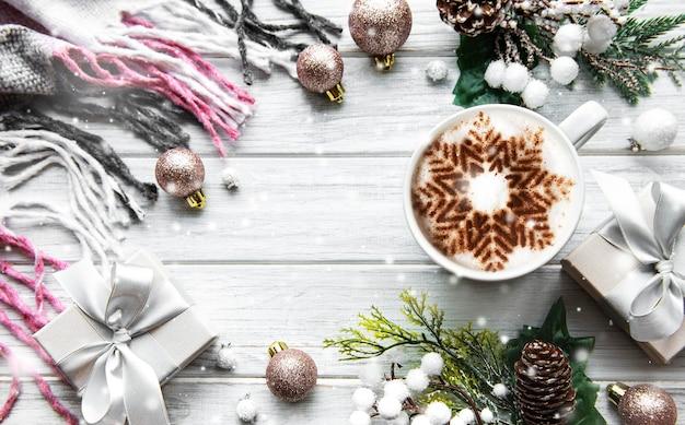 Cornice fatta di decorazioni e caffè con fiocco di neve su superficie di legno bianca