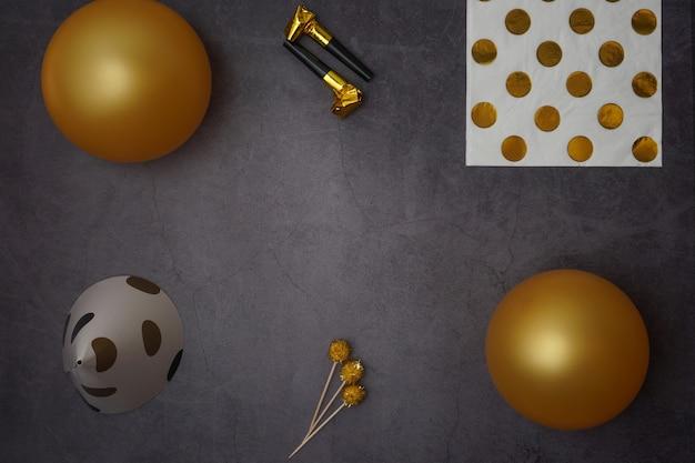 Cornice fatta di diversi oggetti d'oro festa di compleanno su sfondo nero, piatto laici. spazio per il testo.