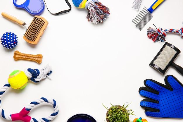 Cornice fatta di diversi accessori per la cura degli animali domestici su sfondo bianco