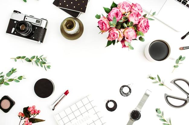 Cornice fatta di accessori moda, cosmetici, fiori di rosa, macchina fotografica, taccuino su sfondo bianco. disposizione piatta, vista dall'alto
