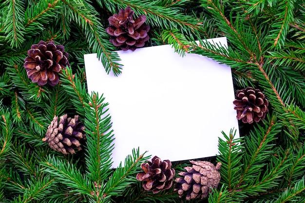 Cornice composta da rami di abete e pigne. il foglio di carta bianco bianco si trova su uno sfondo di verde