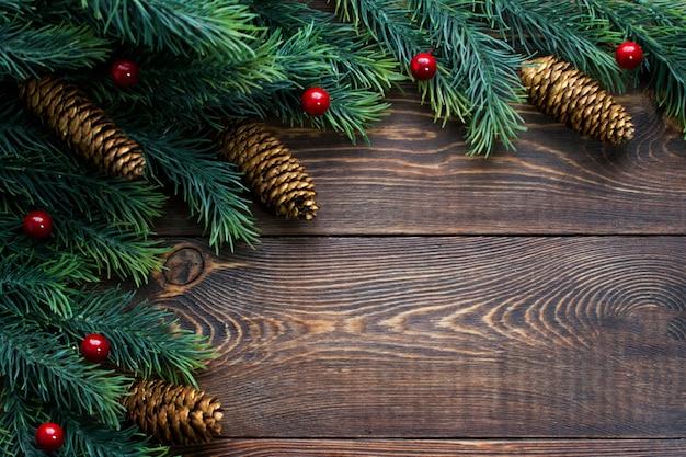 Cornice fatta di rami di abete e bacche rosse di pigne su una superficie di legno marrone