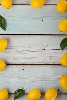 Cornice fatta di limoni fragranti freschi su un tavolo di legno blu