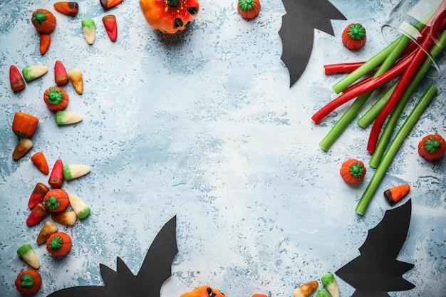 Cornice fatta di caramelle di halloween e decorazioni su blu, vista dall'alto