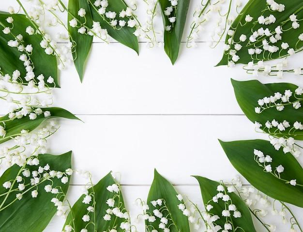 Cornice fatta di foglie di mughetto su un fondo di legno bianco.