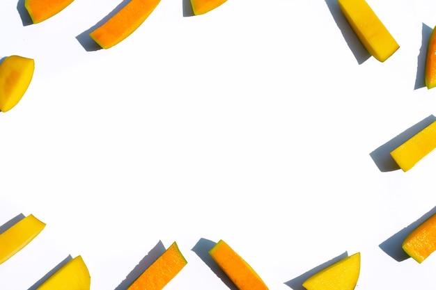 Cornice fatta di pezzi tagliati mango su sfondo bianco.