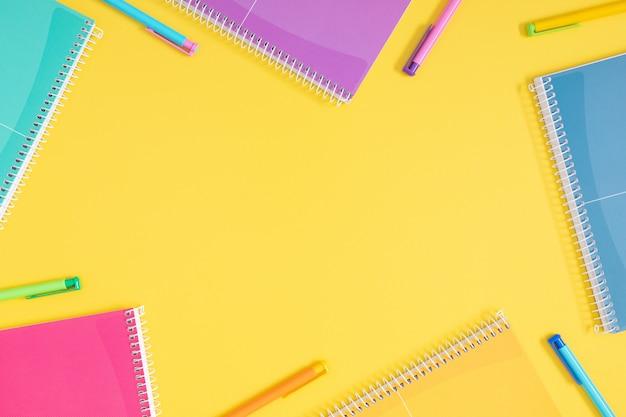 Cornice composta da quaderni e penne multicolori su sfondo giallo vista dall'alto piatta