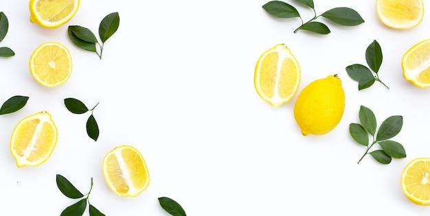 Cornice fatta di limone fresco con foglie verdi su sfondo bianco.
