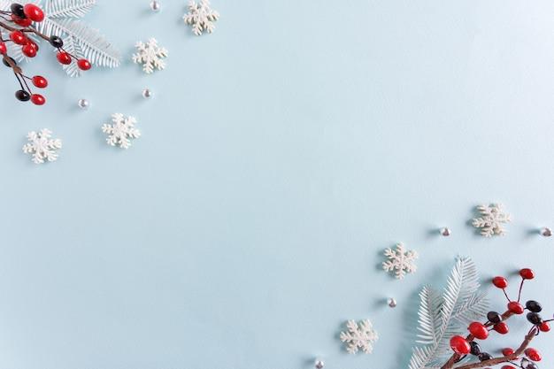 Cornice fatta di fiocchi di neve e bacche rosse su sfondo blu pastello.
