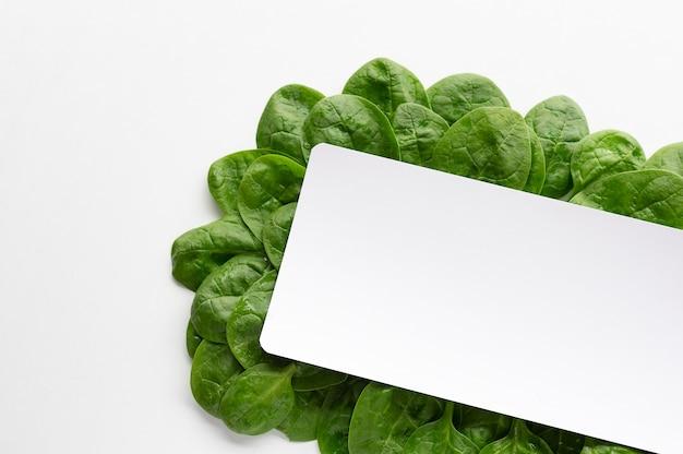 Pagina fatta di foglie di spinaci su sfondo bianco. concetto di cibo creativo.