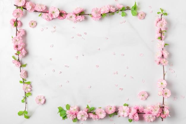 Cornice fatta di rami di fiori di ciliegio rosa primavera su sfondo bianco marmo. lay piatto. vista dall'alto. layout per vacanze o matrimoni con copia spazio