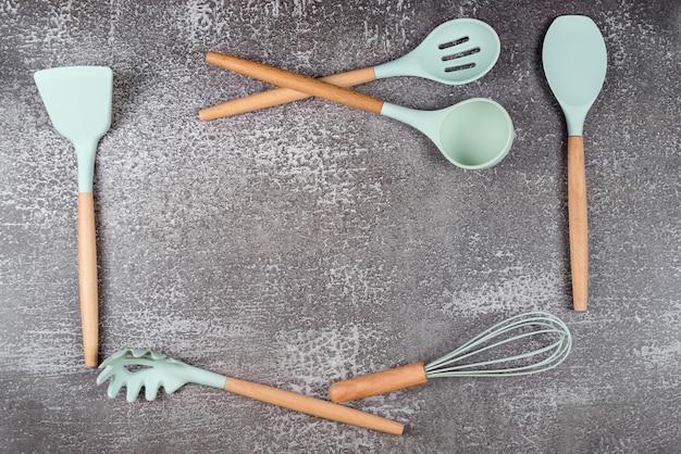 Telaio realizzato con utensili da cucina, utensili da cucina domestica, accessori in gomma menta su sfondo scuro. ristorante, cucina, cucina, tema cucina. spatole e pennelli in silicone, spazio libero per il testo.