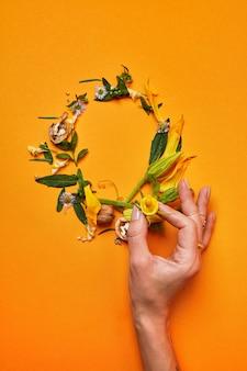 Una cornice di noci, un gambo di zucca, foglie verdi e fiori su uno sfondo arancione. la mano di una donna tiene un fiore giallo. la composizione in rovere flat lay
