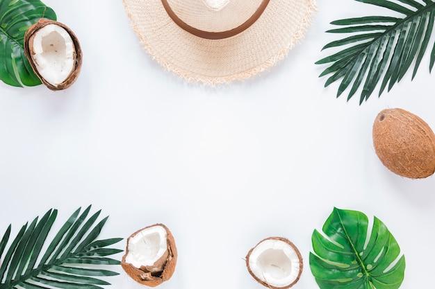 Cornice di foglie di palma, noci di cocco e cappello di paglia