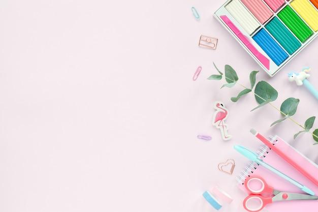 Una cornice di materiale scolastico color pastello su uno sfondo rosa, un posto per il testo. torna alla scuola. forniture per ufficio. lay piatto, vista dall'alto, copia spazio.