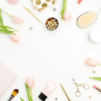 Cornice di fiori di tulipano rosa, accessori e cosmetici su bianco