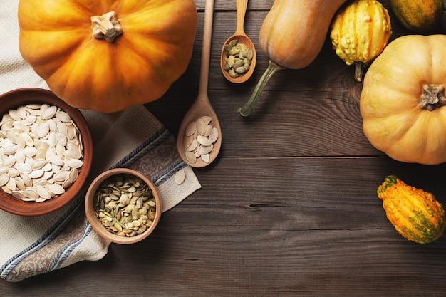 Cornice di zucche di diverse dimensioni su uno sfondo di legno. un piatto e una ciotola di semi di zucca sono in piedi su un canovaccio. due cucchiai con semi. vista dall'alto. copia spazio.