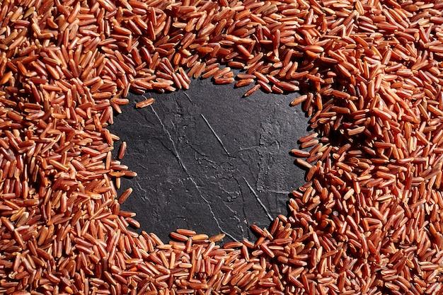 Cornice di chicchi di riso marrone rosso con spazio copia nero, superficie di pietra del tavolo scuro, vista dall'alto