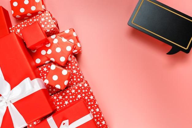 Cornice di scatole regalo rosse su sfondo rosa con copia spazio per la vendita di giorno del testo 11.11 single.