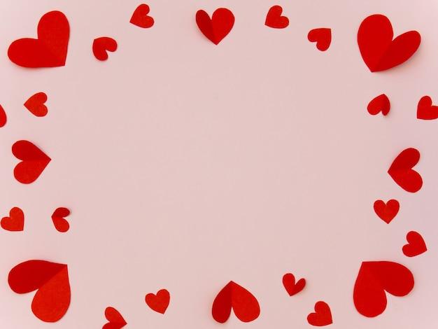 Cornice di cuore rosso su backgrond rosa con copyspace per biglietto di auguri di san valentino.