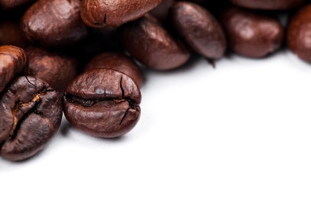 Cornice di chicchi di caffè tostati isolati su bianco