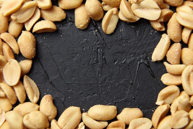 Cornice di arachidi pelate tostate closeup, spuntino di birra salata su sfondo nero