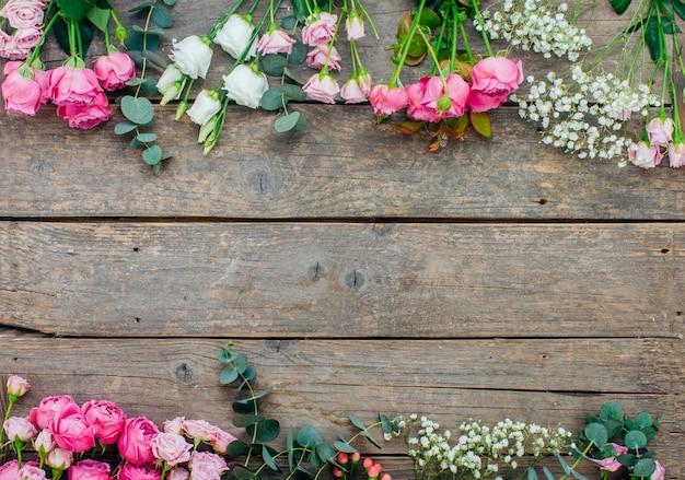 Cornice di fiori di rosa, eucalipto, eustoma, gypsophila su fondo di legno del mestiere con spazio vuoto per testo. vista dall'alto, piatto.